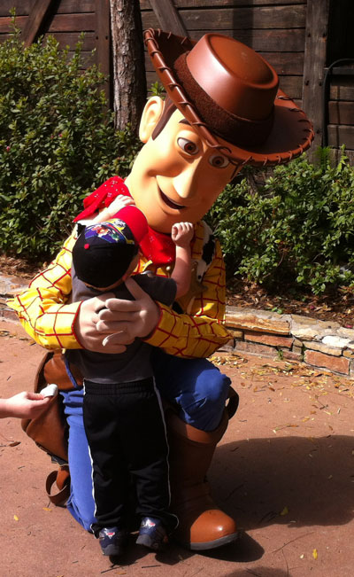 Woody from Toy Story hugs a small child