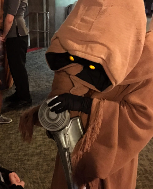 Jawas trade from a container slung over their shoulder