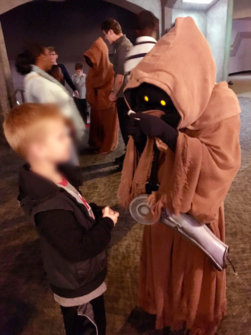 Young boy seen trading with jawas at Star Wars Launch Bay