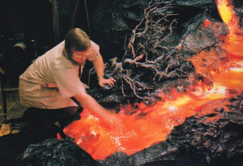 A technician dips his hand into the lava from the Universe of Energy volcano